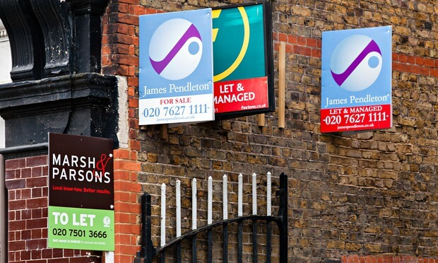 estate agents boards against house wall